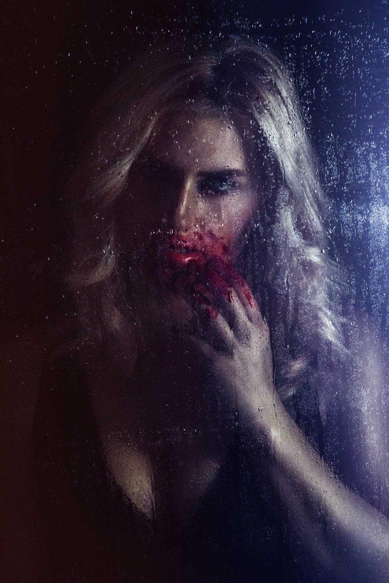 Düsteres Photoshooting mit Model und Kunstblut vor nasser Fensterscheibe